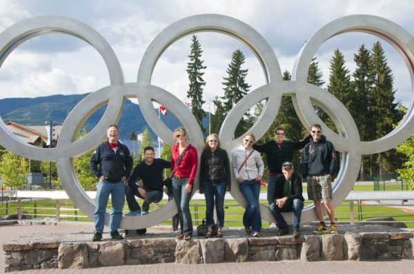 Human Powered Racing Athletes standing in front of the Olympic Rings at Whistler Park during 2013 camp.