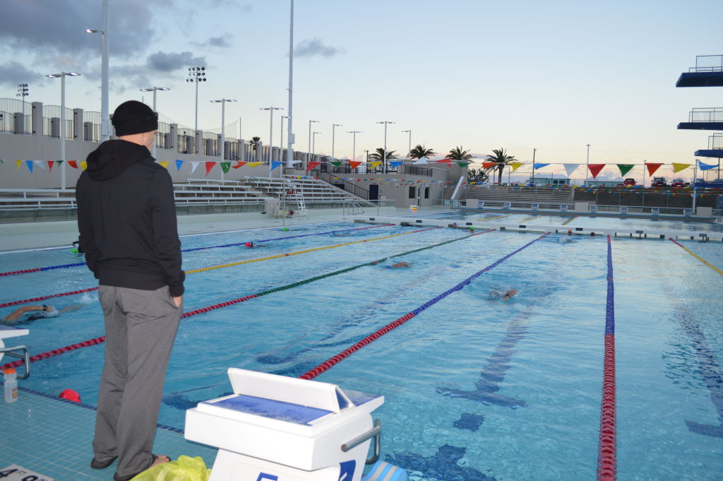 Mike Neill standing on deck of Bermuda National Stadium pool coaching Neill/Blake camp in 2015