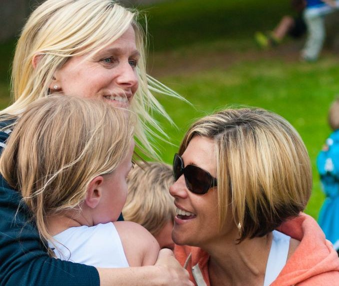 Sandy, Nadine and Sara Wilson hugging at the finish of the Victoria Youth Triathlon