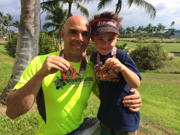 Jay Krieger and his son show off their medals at the Lavaman Triathlon in Waikoloa, Hawaii at the Lavaman Triathlon