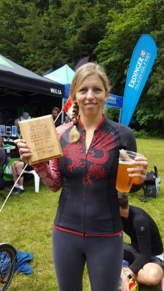 Kara Hobby drinking beer at the finish line of the Shawnigan Lake triathlon while drinking a well deserved beer.