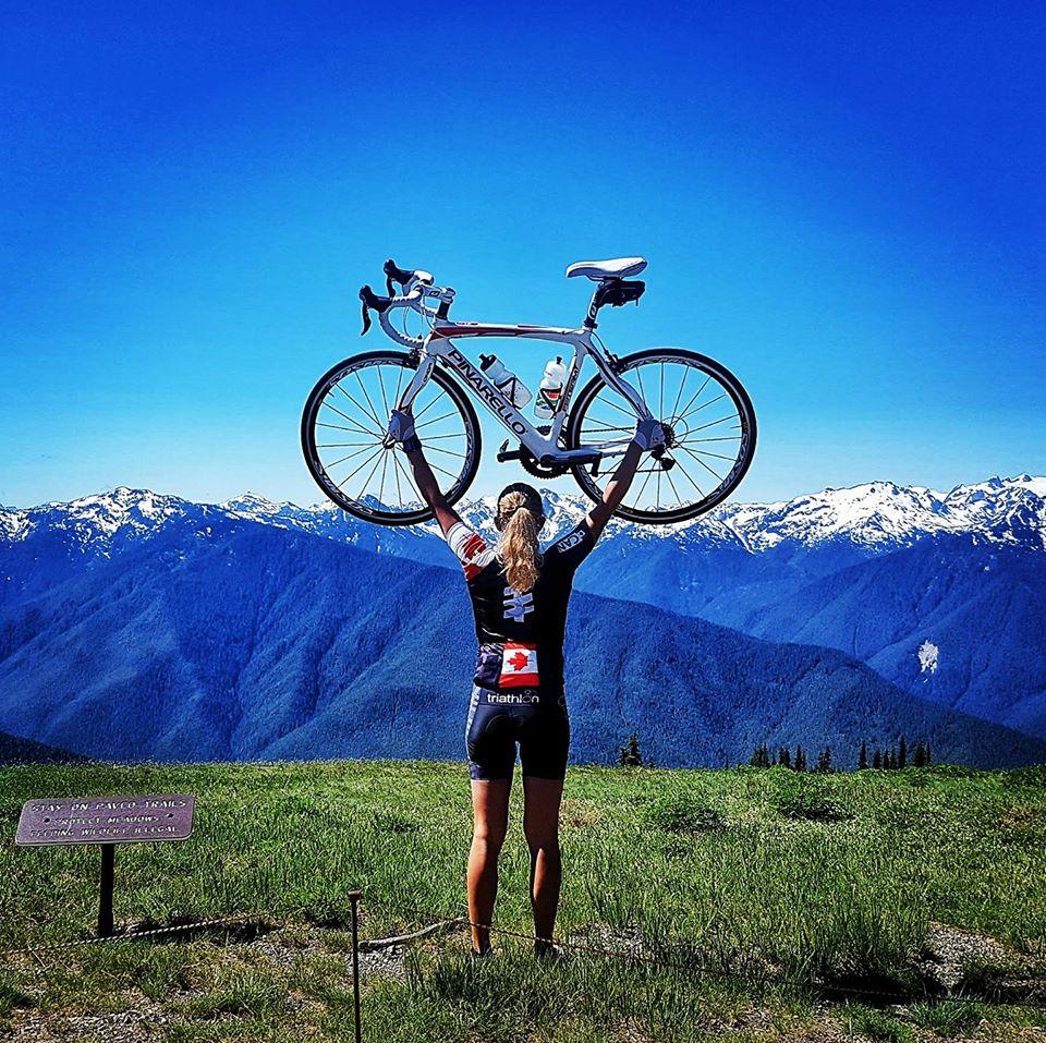 Kara Hobby holding bike above her head at the top of Hurricane Ridge on Canada Day