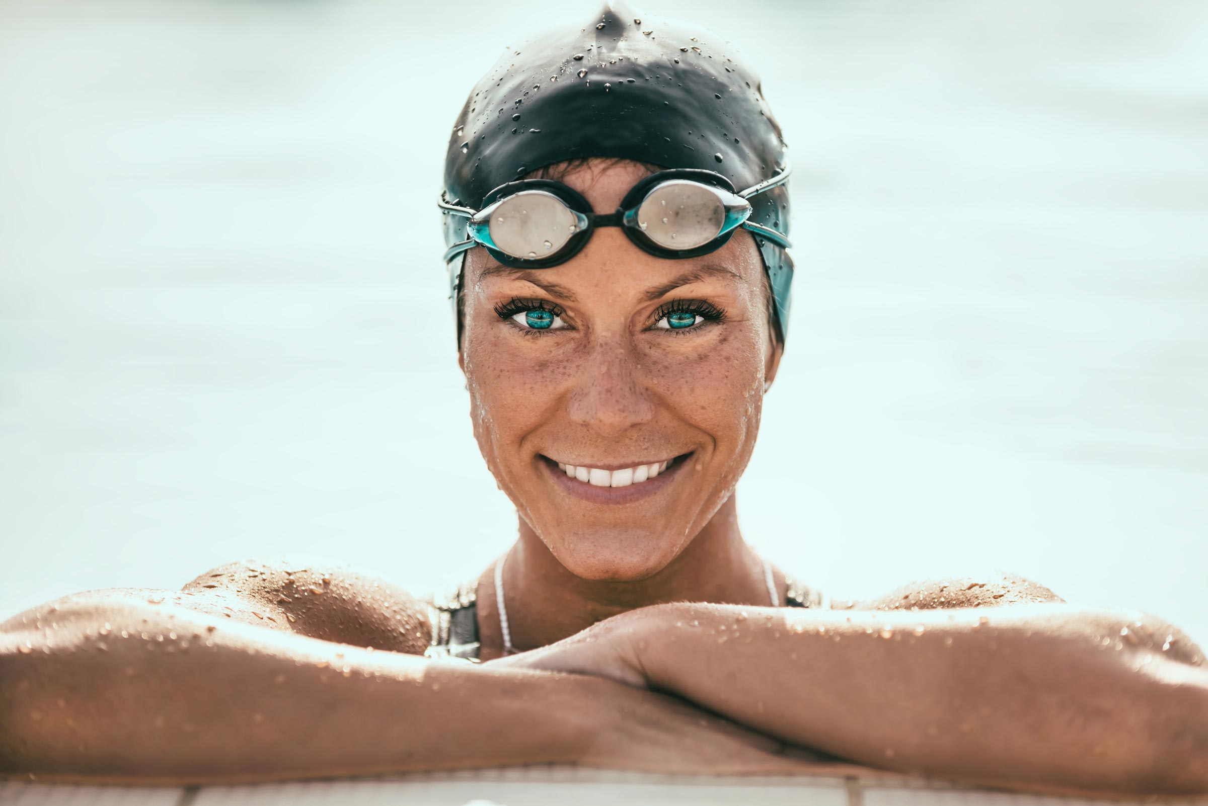A woman swimmer rests at the edge of a pool with her goggles up, in between training.
