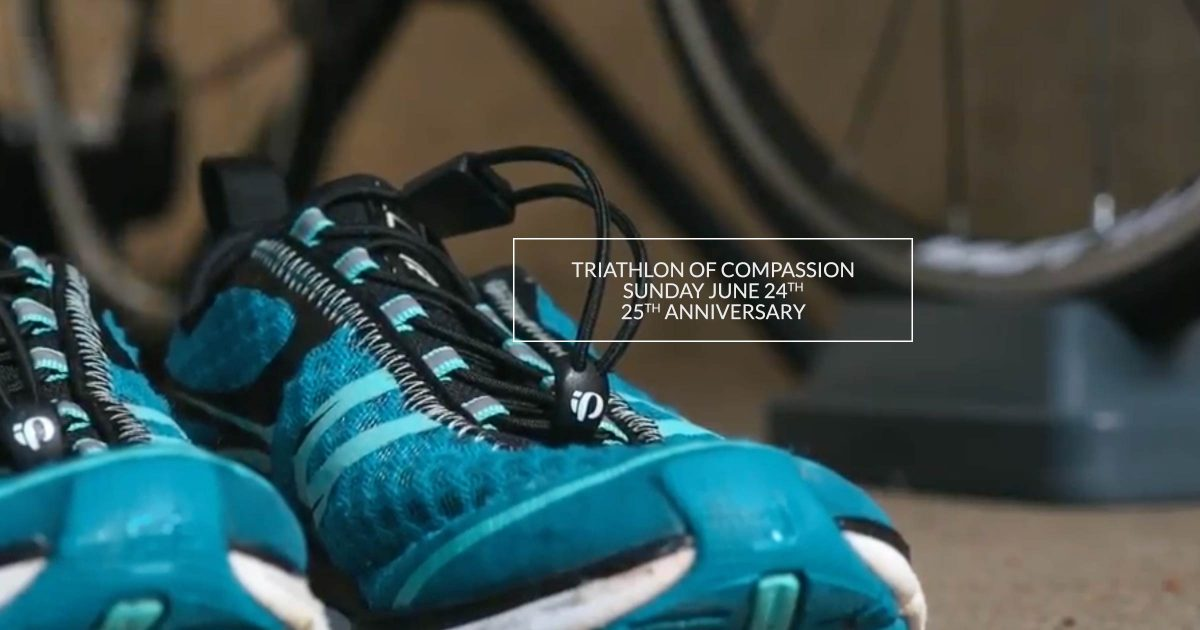 Runners sit on the floor, beside a training bike: Triathlon of Compassion June 14