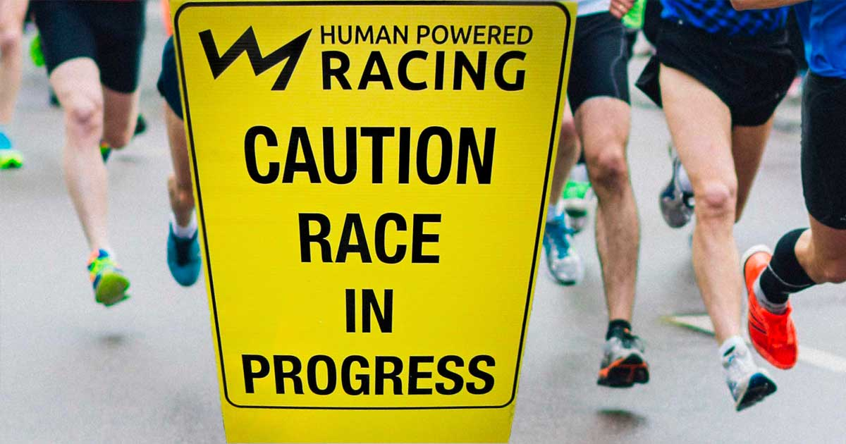 Runners run by the Human Powered Racing sign: caution race in progress.