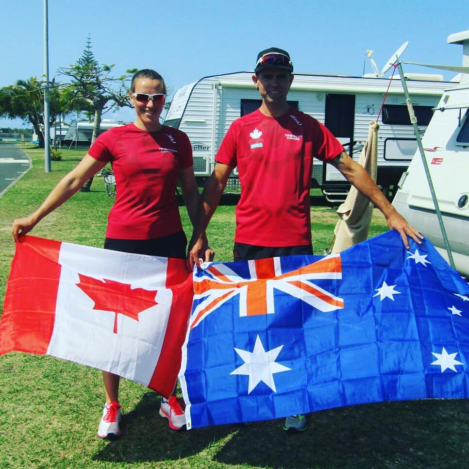 Barb Rober and Shane Russell holding flags at the ITU Triathlon World Championship in Australia