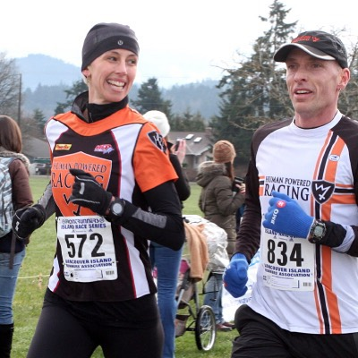 A woman and man running outdoors. The woman is on the left and smiling over at the man who is looking ahead. Both are in orange, black, and white long sleeved running tops and we can see from their thighs upwards. They also both have race numbers pinned to their stomachs. There are evergreen trees, mountains, a grey sky in the background and they look to be on a grassy field.