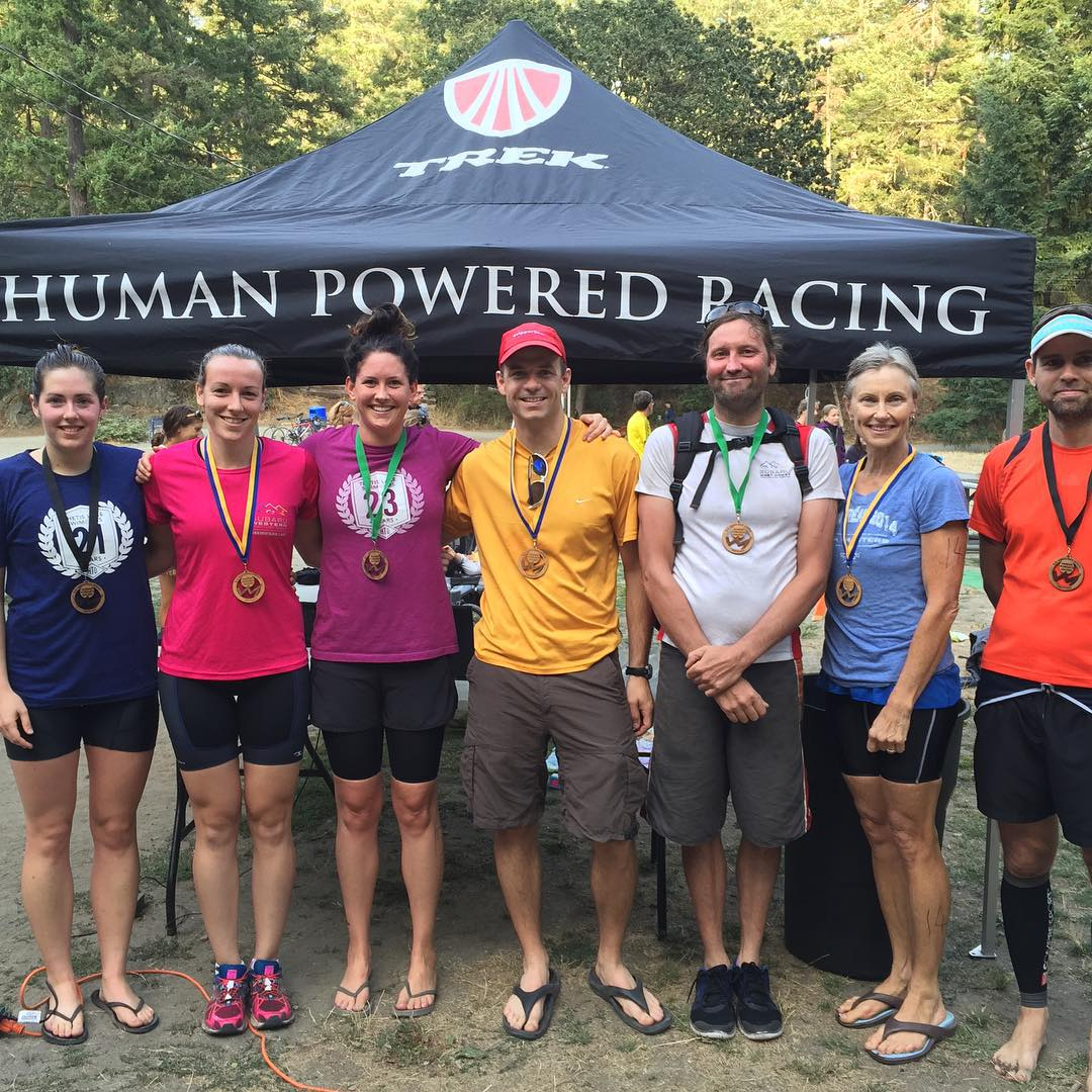 "A line of seven racers in shorts and tshirts with medals around their necks. They are all smiling, and standing in front of a black tent that says ""Human Powered Racing."" There is sand underneath them and there are evergreen trees in the background. It is a sunny day."