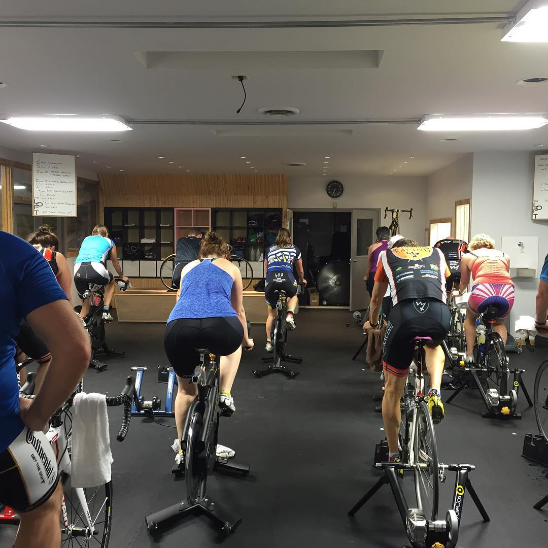 A room full of people on stationary bikes. The view is from the back of the room so we do not see peoples' faces. The floor is black and the walls are white, and the lights are rectangular and flat in the ceiling.