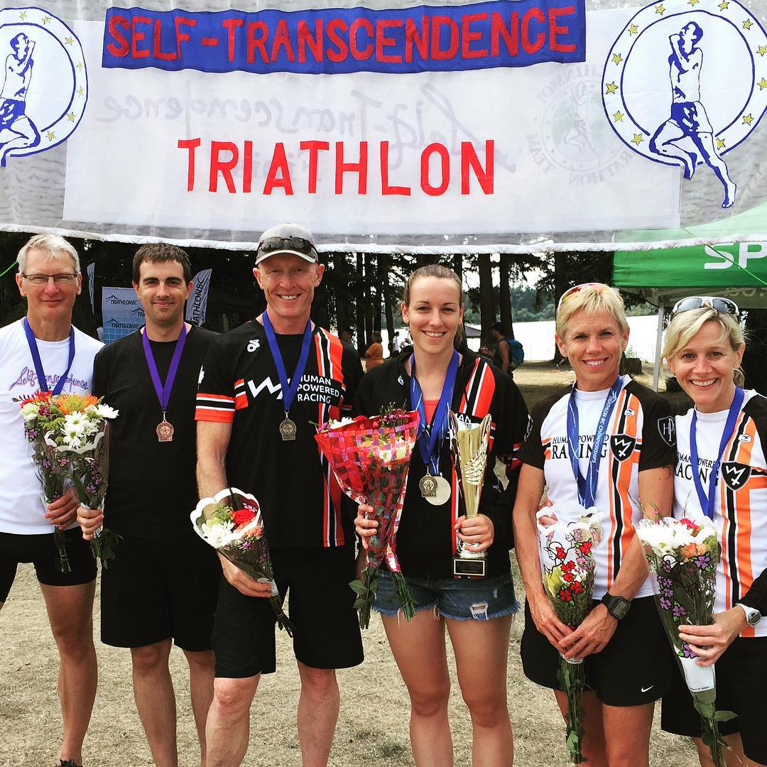 "Six racers with bouquets of flowers and metals handing around their necks are standing in a row on sand and smiling. Behind them is a white banner that says ""Self-Transcendence Triathlon"" in red capital letters."