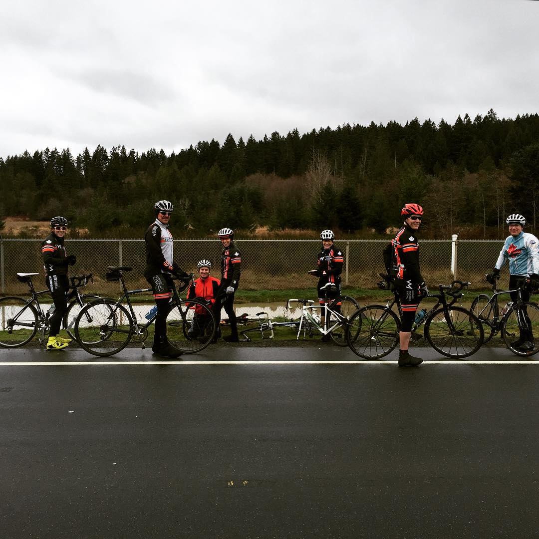 A group of bikers on the side of a wet road with a green field and then hilly tree covered terrain in the background. It is a grey, cloudy day. They all have their bikes with them, and one of the bikers is kneeling in the grass.