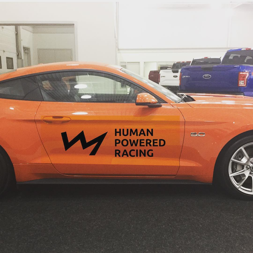 "A photo of the right side of an orange mustang that has ""Human Powered Racing"" and their logo printed in black on the door. The logo is a zig zag line in the shape of a mountain range silhouette. The car is in a white room with a dark grey floor. There are trucks on display in the background to the right."