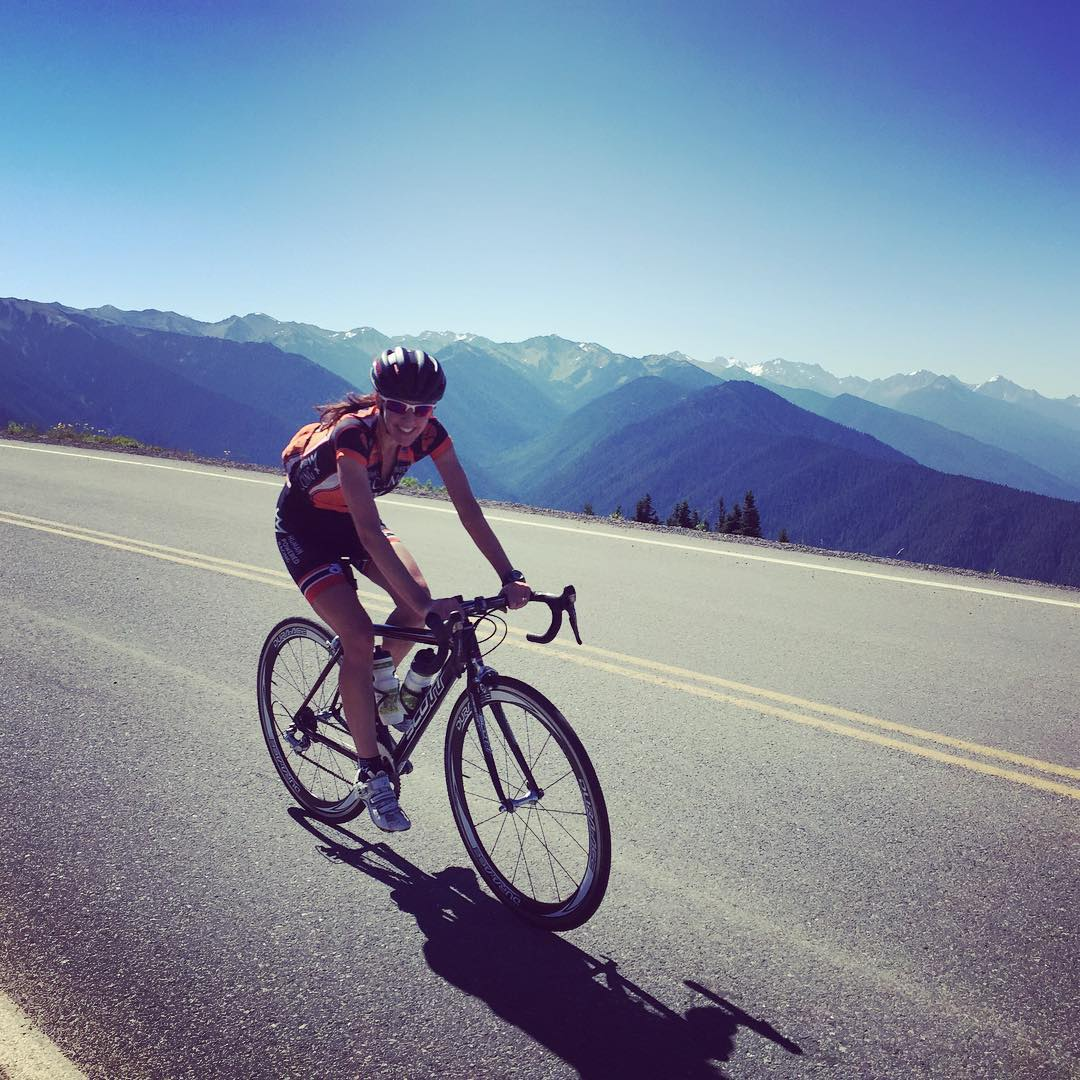 A woman riding a bike along a road. She is in full bike gear, and smiling forwards at the camera. Behind her are mountains that look blue and recede into the distance, and the sky is bright and blue and clear.