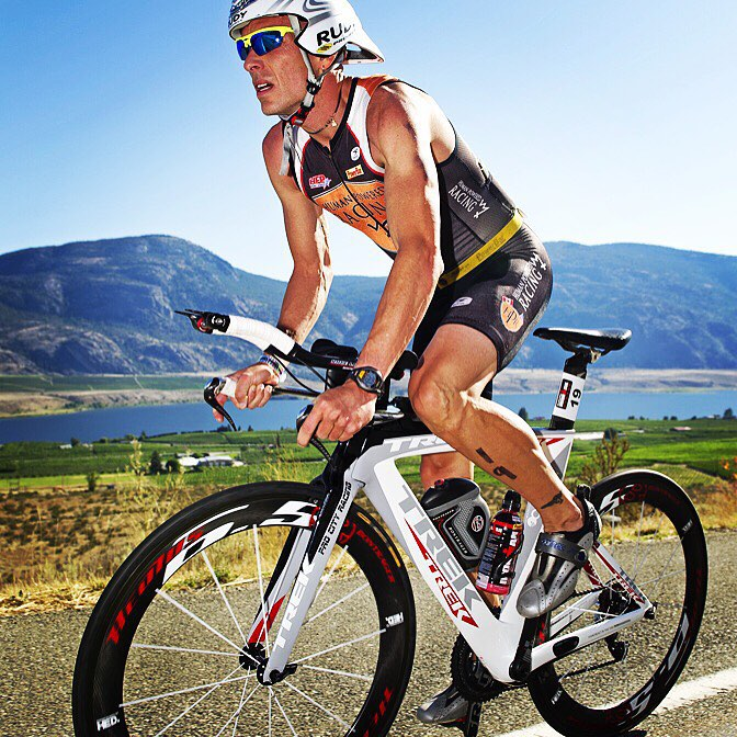 A man on a white bike in a black triathlon suit and a white helmet. He is leaning over the handle bars and is standing up on the pedals instead of sitting on the bike. He is biking on a road and there is a grassy stretch directly behind him with a lack and mountains in the distance. It is a clear, sunny day.