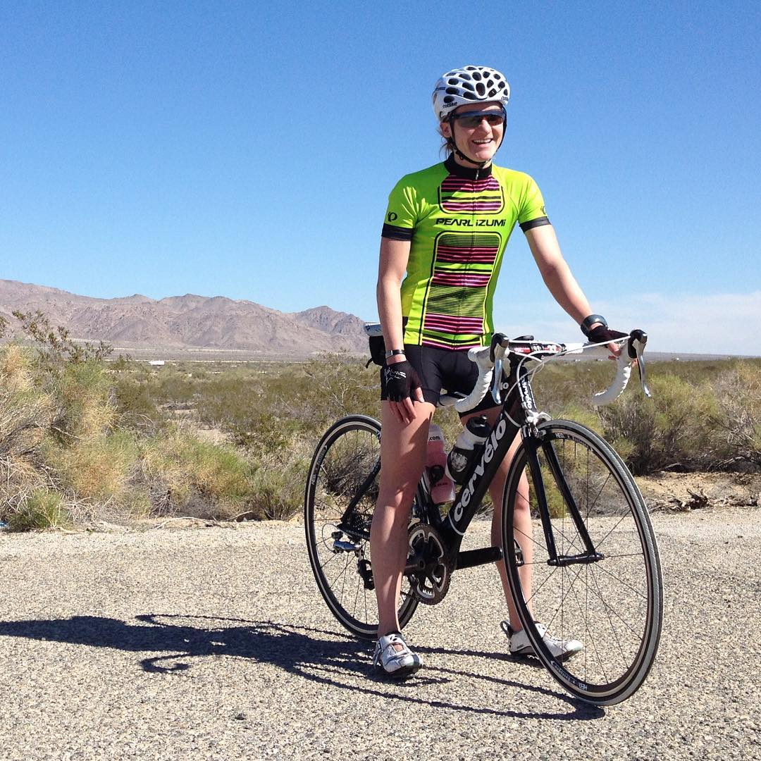 A woman in a lime green tshirt and biking shorts with a helmet on a bike. Her feet are on the ground stabilizing the bike, and the landscape around her is dry with gravel sparse bush, brown mountains in the distance, and a blue sky.