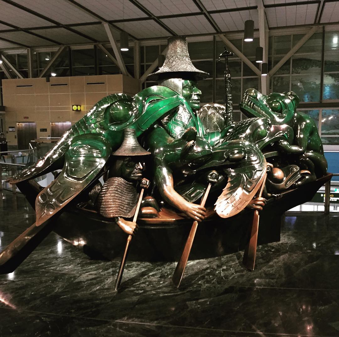 """The Spirit of Haida Gwaii: The Jade Canoe"" in the Vancouver airport. It is a jade sculpture of a man and man animals in a canoe that has three paddles on either side. This photo is of the right side. The jade is green on the upper half, but touching has turned the bottom half a bronze or brown colour. The floor is marble, and looks a bit water like."