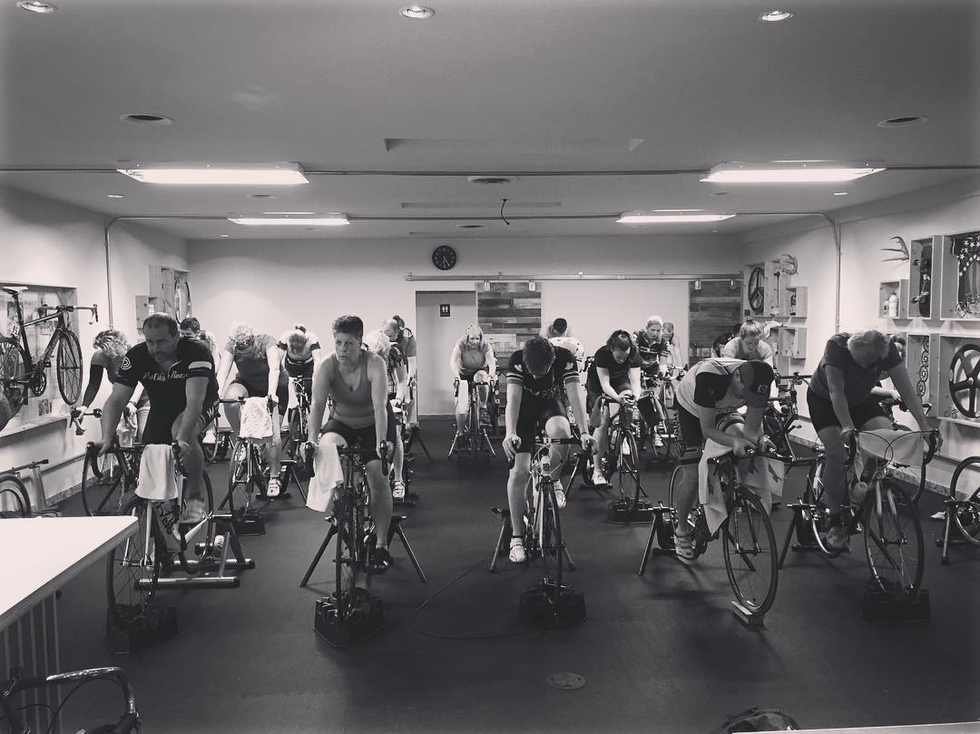 Black and white photo of a room full of people on stationary bikes.