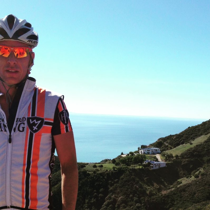 A man is on the far left with his right shoulder cut out of the photo. He is wearing a white vest with an orange vertical strike on his left side. He is wearing sunglasses and a helmet. There is a rocky outcrop behind him and then a blue sky.