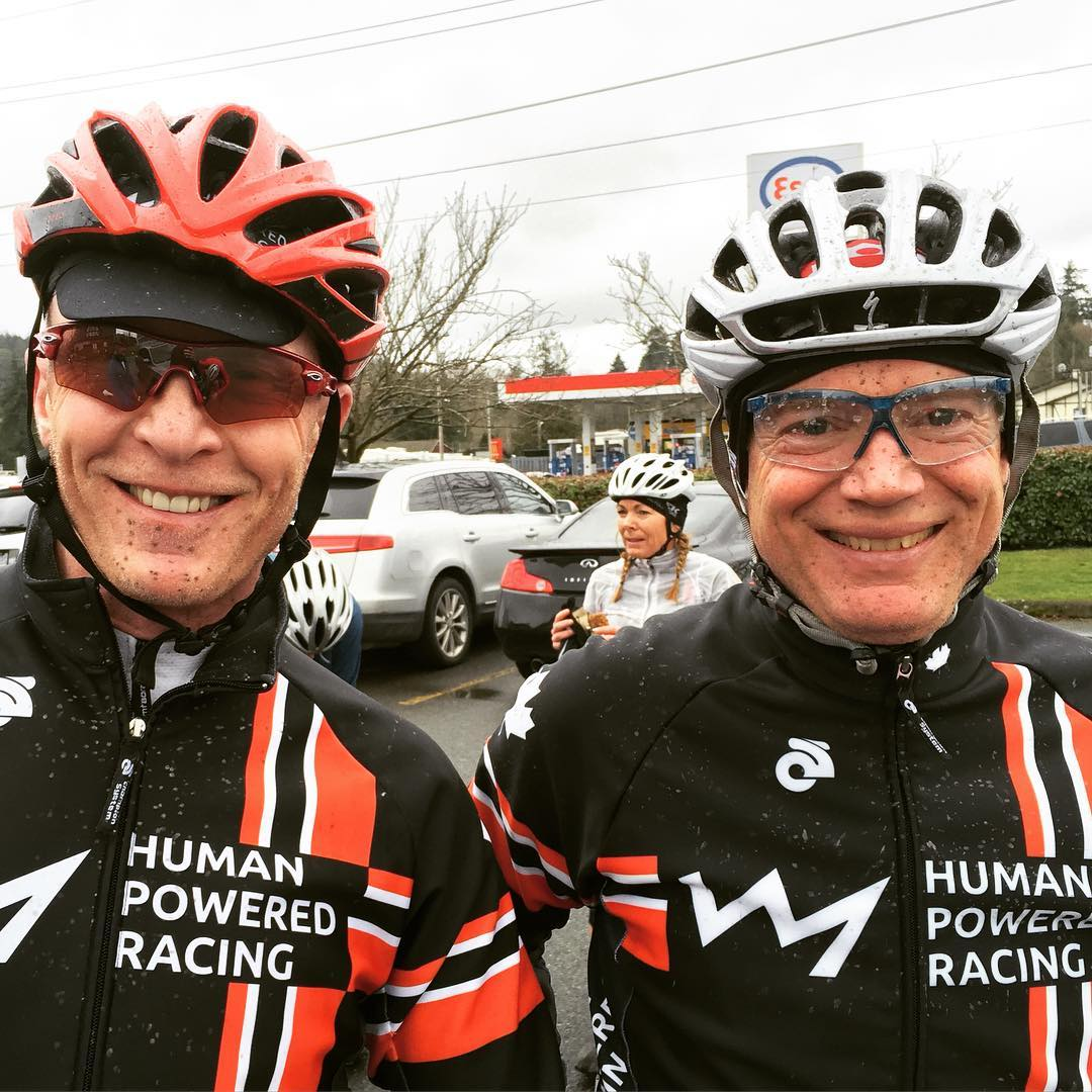Two men from the chest up in a parking lot. Both of them are smiling, splattered with mud, and wearing biking gear. It is a grey day.
