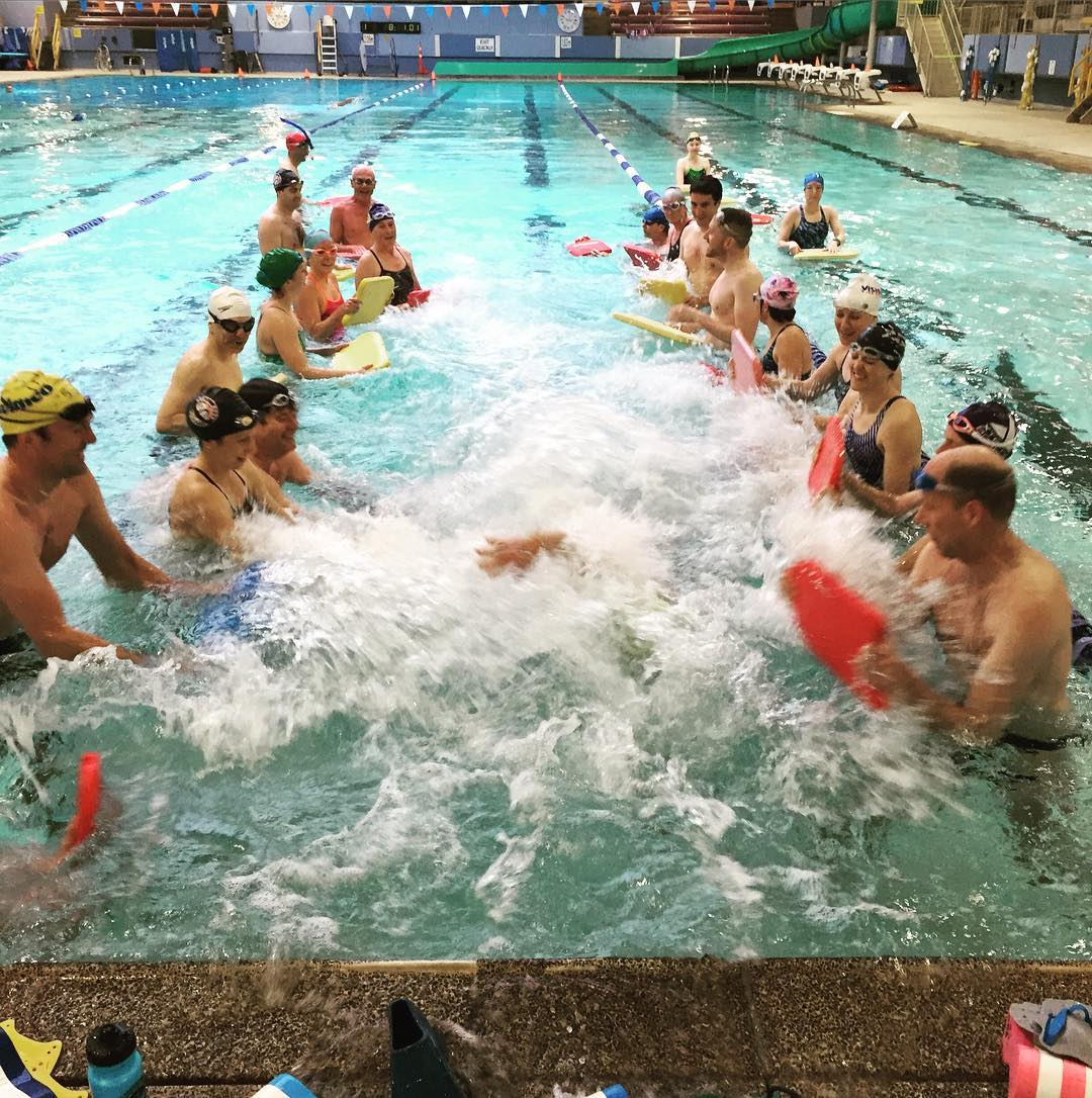 Two rows of people in a pool using kickboards to create turbulent water for a person who is swimming down the middle.