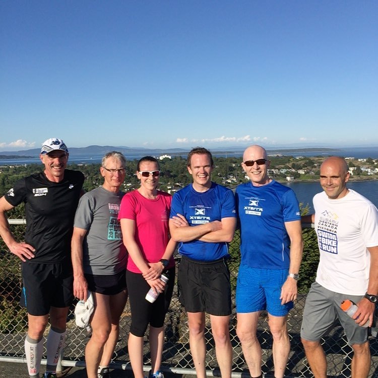Six people standing in front of a view with a blue sky, mountains, and green city scape. They are all in running gear and looking at the camera.