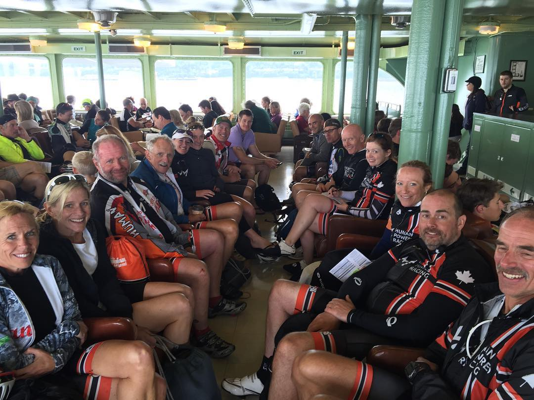 A group of people sitting in two rows inside a ferry mostly wearing the HPR colours red and black. They are smiling, and turning their heads to face the camera. Daylight is coming in through windows at the far end of the ferry.