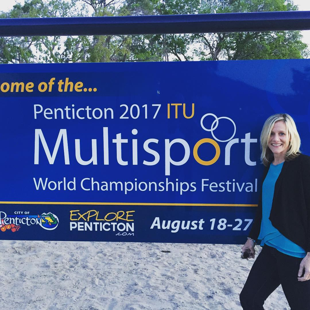 "A woman standing to the right by a blue sign that says ""Penticton 2017 ITU Multisport World Championships Festival."" It is on a beach and there are trees in the background."
