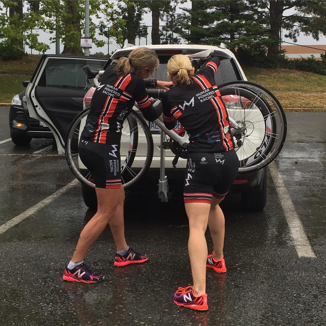Two women with their backs to the camera working on a bike rack, which has two bikes on it and is attached to the back of a white car.