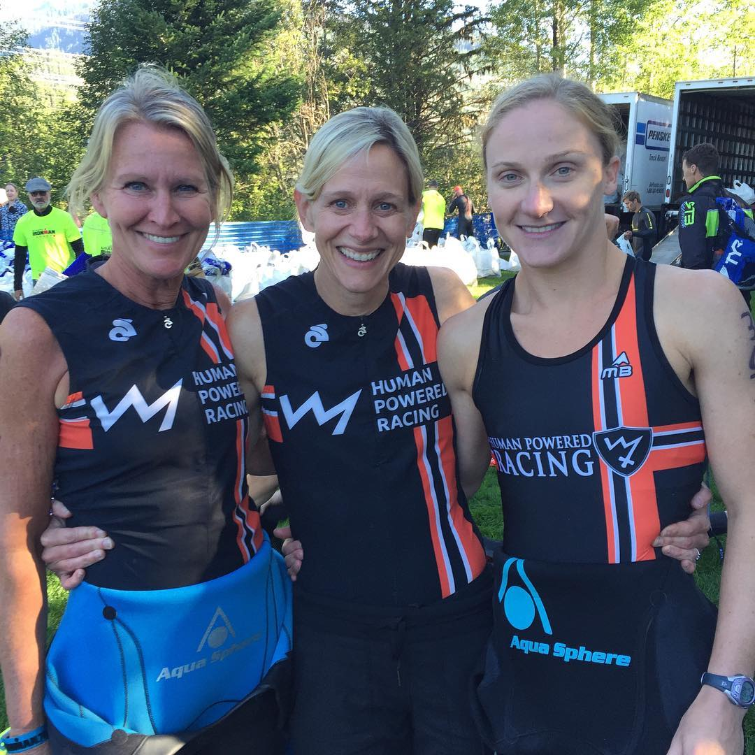 Three women standing shoulder to shoulder with their arms around each other and smiling. They are all in black and red HPR triathlon bodysuits. There are green trees in the background, and glimpses of sunny between the trees.