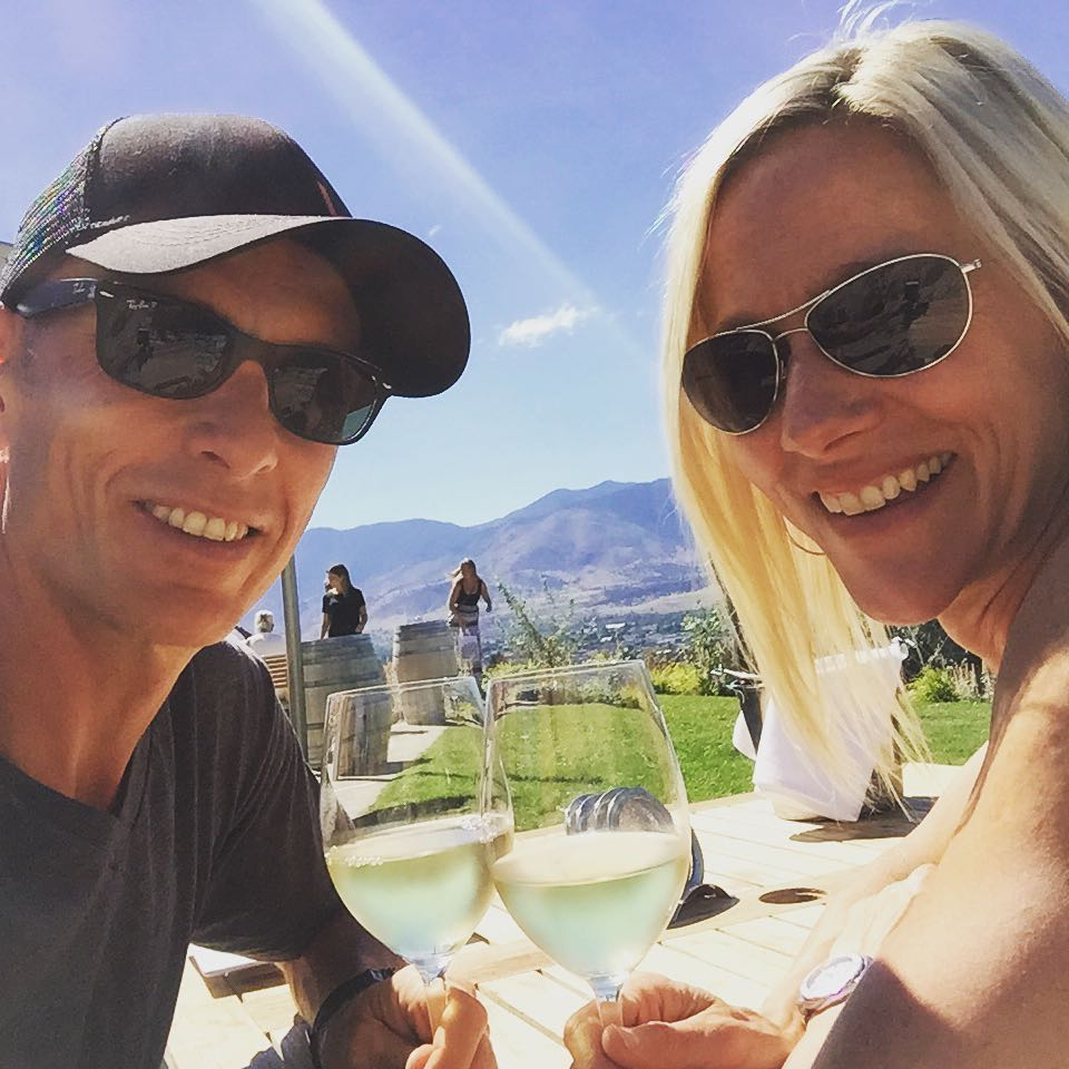 A man and a woman from the shoulders up with the man on the left and woman on the right. They are clicking two glasses of white wine. There is green grass and a view of dry mountains behind them. The sky is blue, and both are wearing sunglasses. They are both smiling.