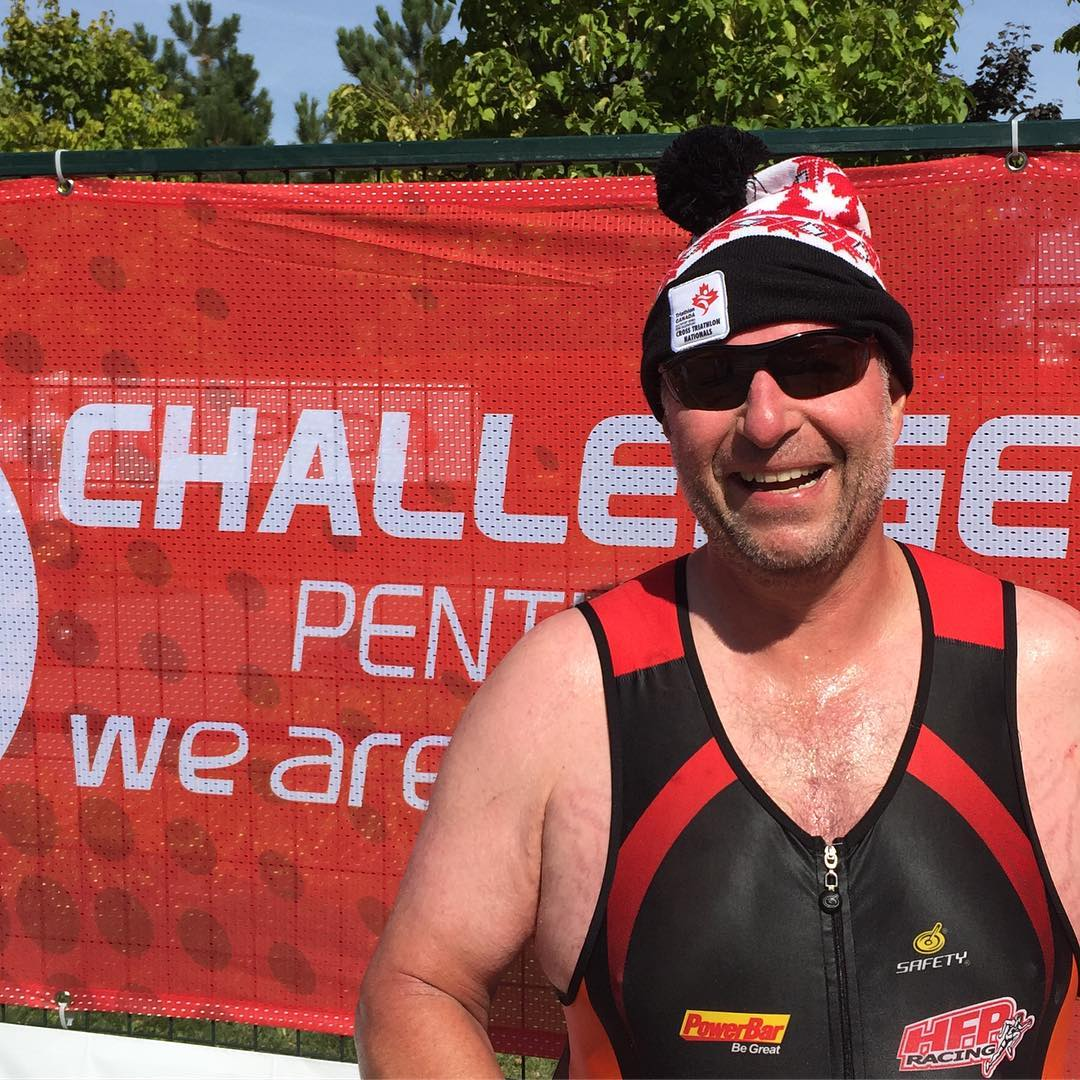 "A smiling, sweaty man with a red and black tuq on, and a red and black triathlon bodysuit. We see him from the chest up. Behind him is a red, gauzy sign that says ""Challenge Penticton"" and something else we can't read. There are trees and blue sky behind the sign."
