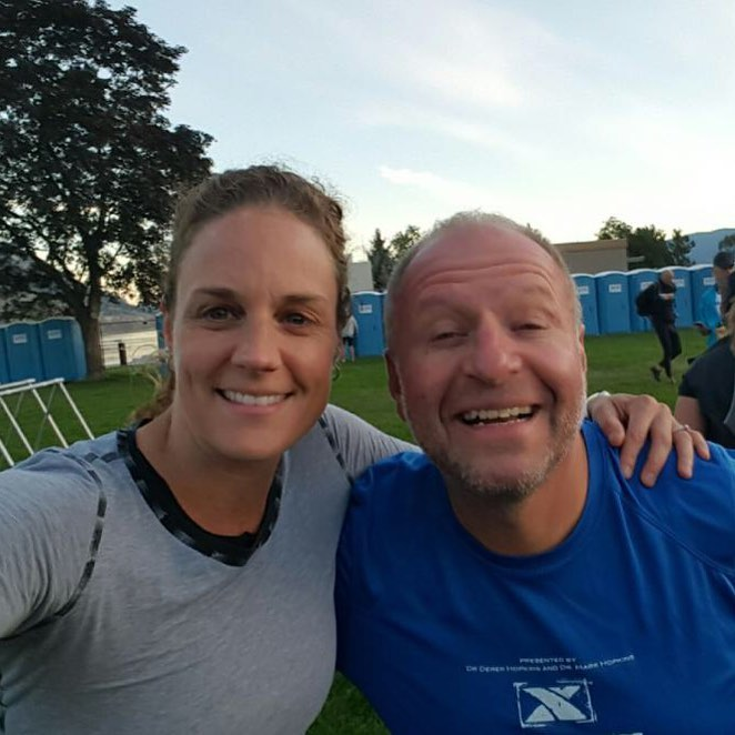 Two people from the chest up. A woman in a grey long sleeved shirt has her left arm around the man in a blue shirt who is to her left, and has her right arm straight out to take the selfie. Both are smiling widely. The sky is a light blue with white clouds and there is a green soccer field in the background and a tree behind them to their right.