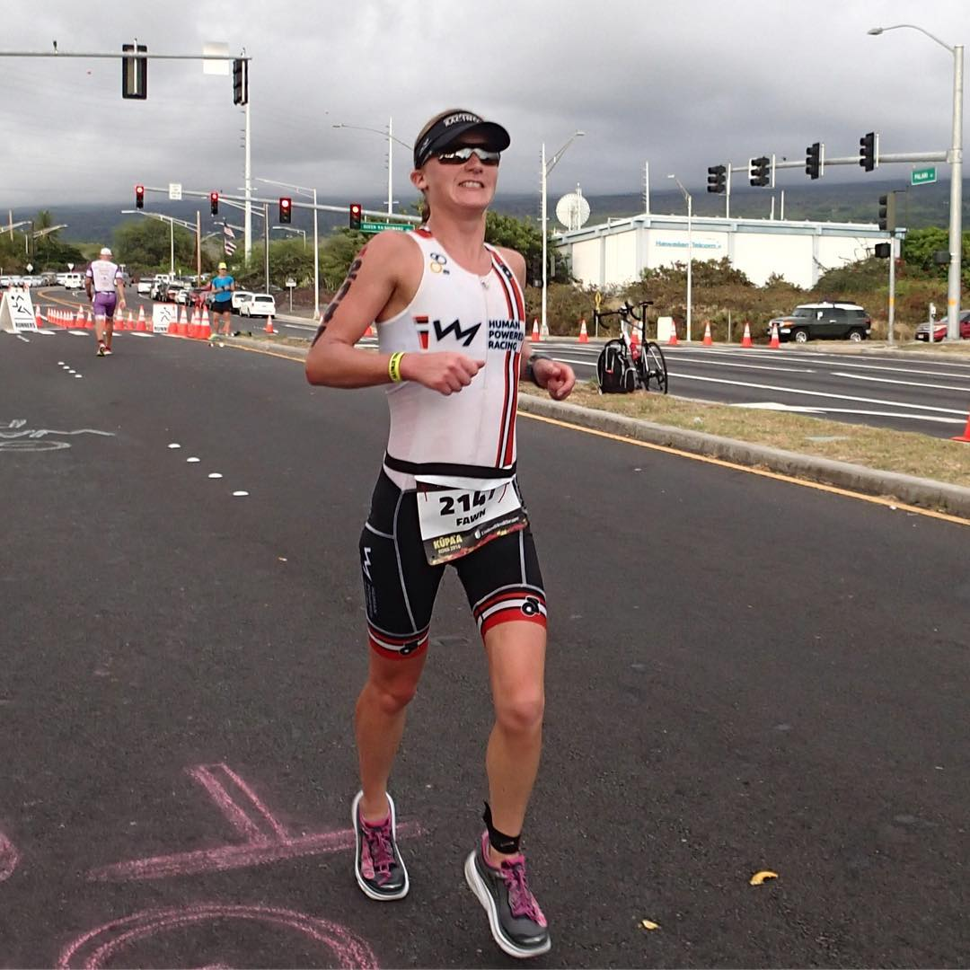 A woman running towards us on a road. She is wearing a triathlon bodysuit in the HPR colours of red, white, and black. She is also wearing a black visor. It is a grey, cloudy day, and there is a four way stop cluttered with orange directional cones in the background