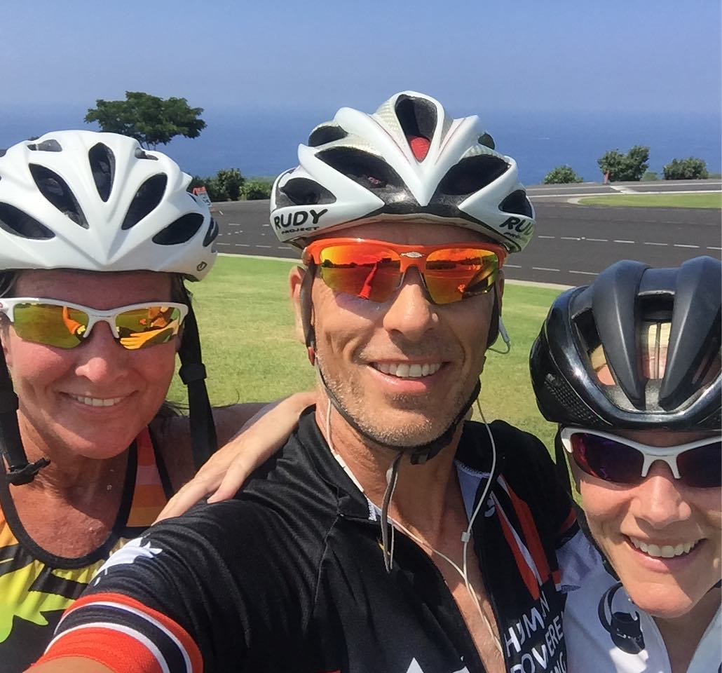 Three people in helmets and sunglasses are shoulder to shoulder and smiling. We cannot see below their shoulders. They all look to be wearing exercise shirts. There is a stretch of green grass and then a road behind them as well as some trees in the distance. They sky is a greyish blue.