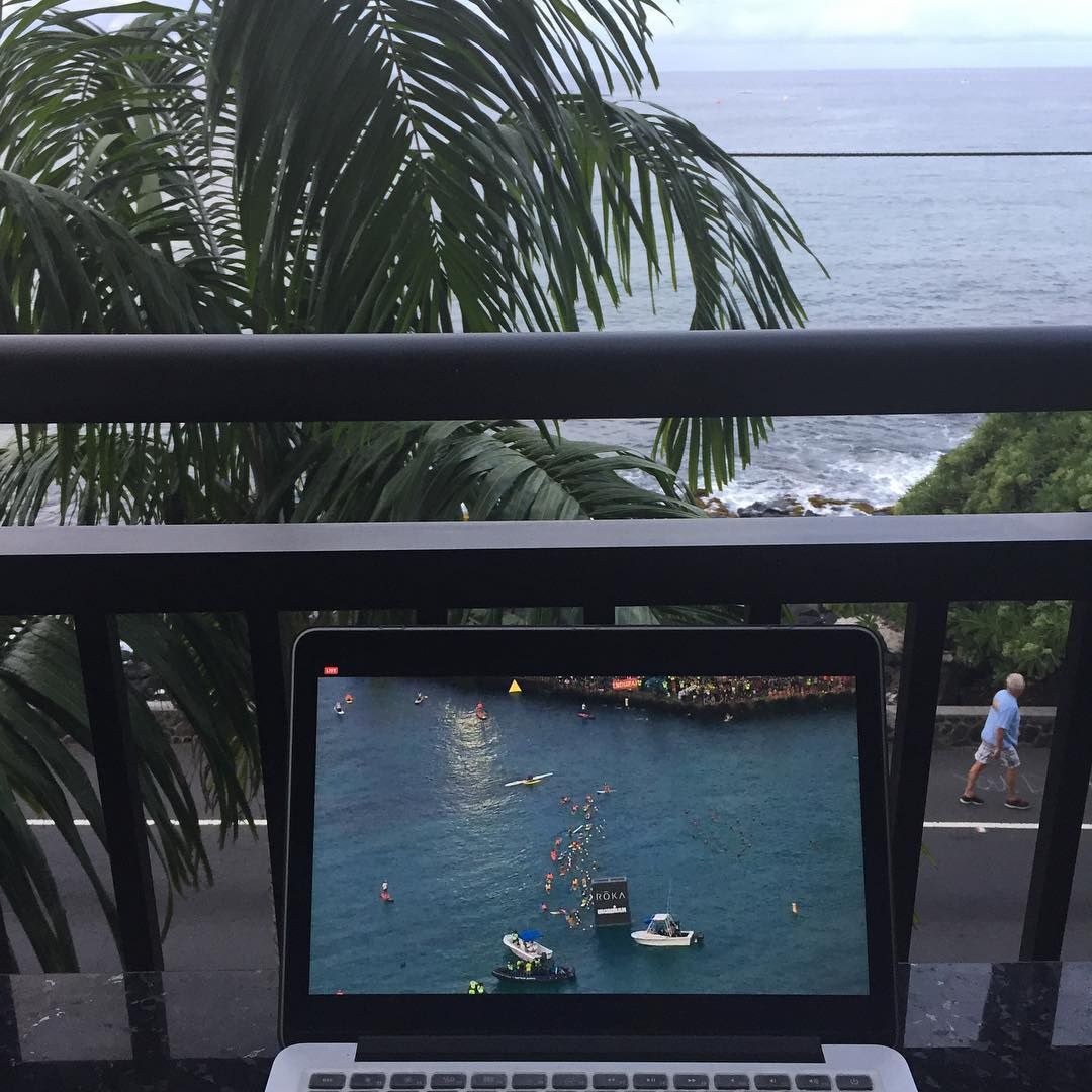A laptop that shows a blue body of water with many swimmers in it is in front of a black metal fence on a balcony overlooking a palm tree and ocean. It is daylight.