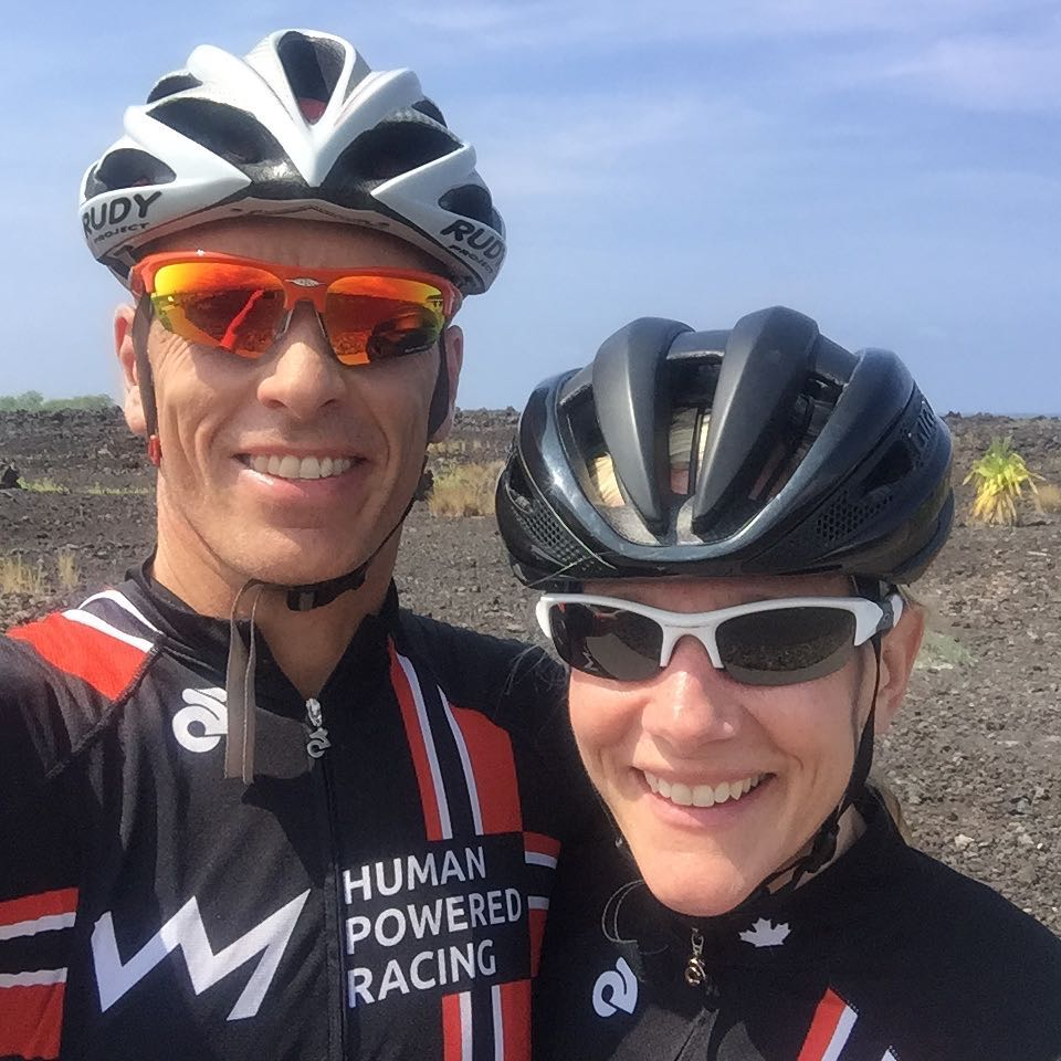 A man and a woman from the chest up with the man on the left and the woman on the right. Both are smiling with HPR black and red tops, sunglasses, and helmets. The background is a dry grassy field and a blue sky.
