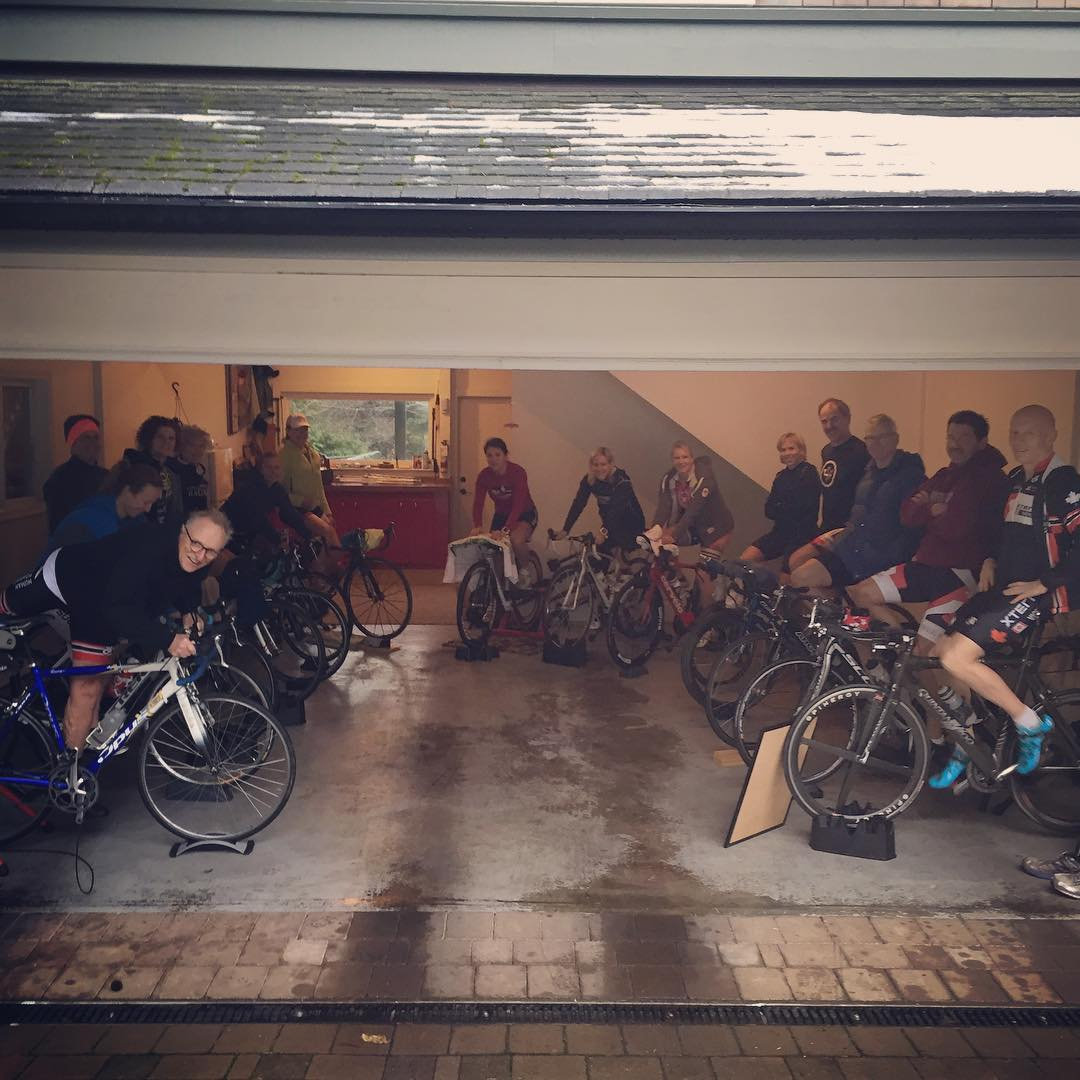 A group of people in biking shirts and shorts on stationary bikes in an open garage in a U shape. The pavement outside the garage is wet. Red cupboards are visible in the background through the back of the garage.