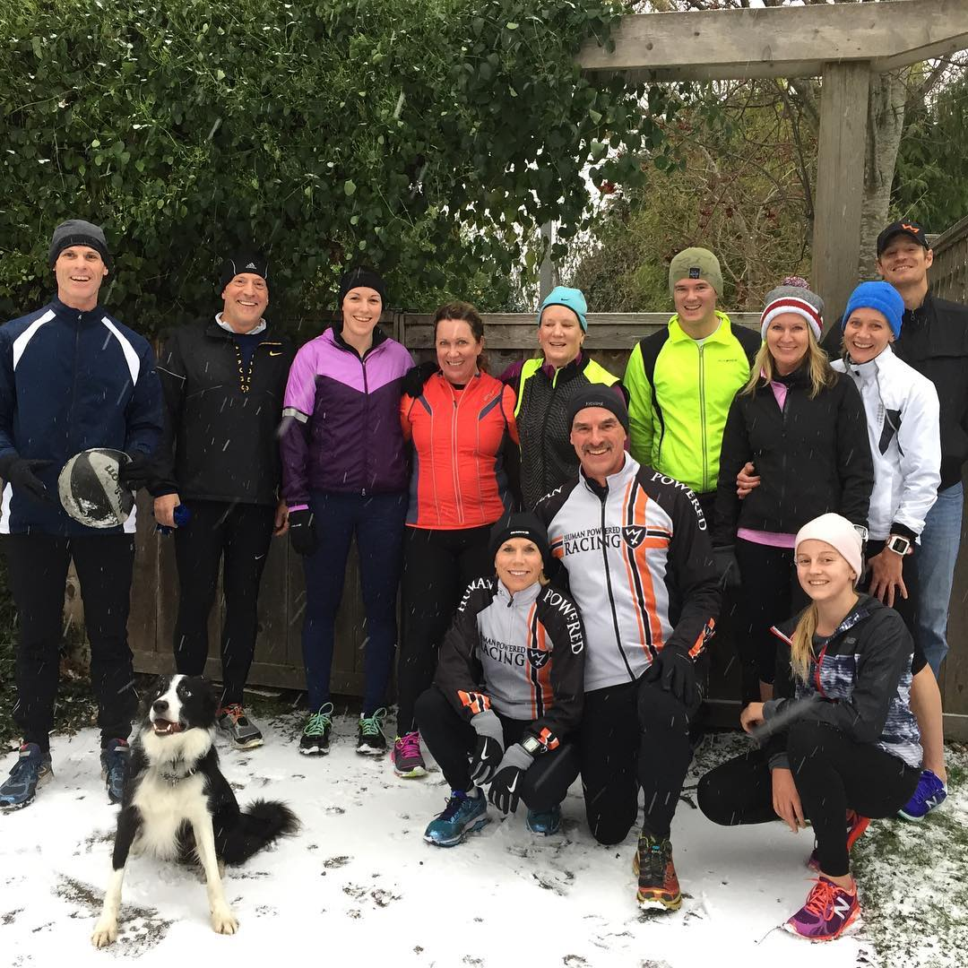 A group of people standing in front of a dark brown fence with a tall green bush behind them on the left. The ground is covered in a thin layer of snow and everyone is smiling a wearing warm running gear. Three people are crouching in the front, and a black and white border collie is sitting in the front on the left.