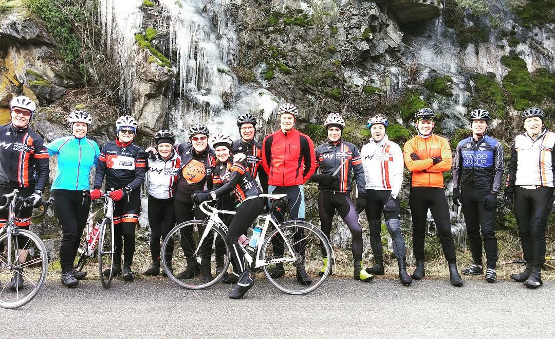 Group of bikers standing in front of a rock wall on the side of the road. It is covered in icicles. They are all standing, and some have their bikes.