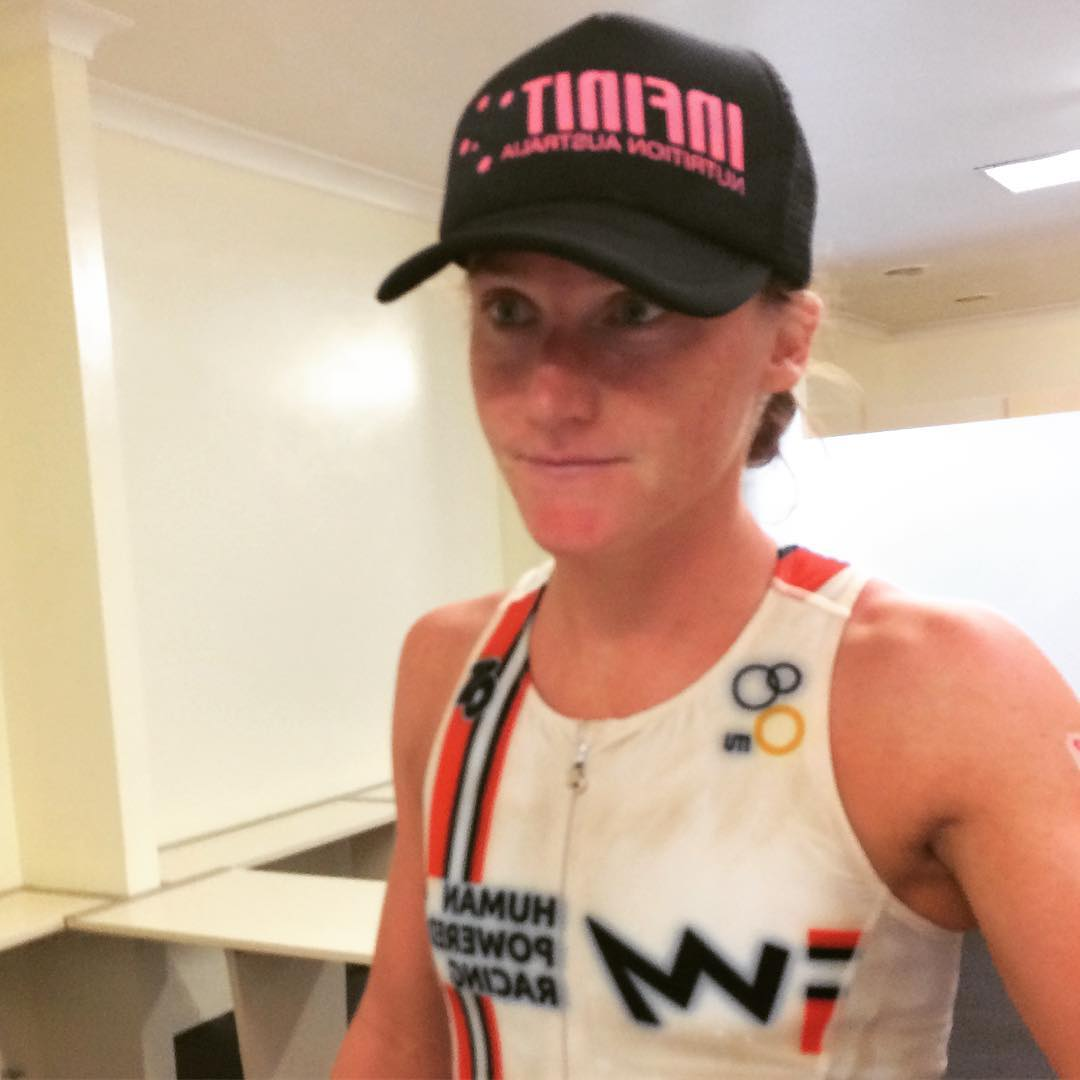 A woman's torso and face taken slightly to her left. She is wearing a black cap, and is sweaty and flushed. She has a red and white HPR tank and her lips are slightly drawn in. She looks focussed.