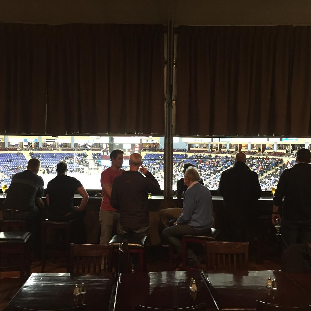 This is a photo of a group on men sitting on bar stools in front of a bright window. Beyond the window is a stadium, and the risers on the other side are visible in the photo. The men are looking away from the camera and into the stadium.