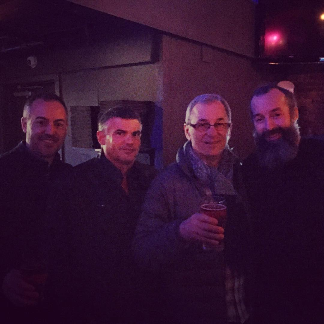 Four men inside a pub, and the lighting is tinged pink. They are standing shoulder to shoulder smiling. The one second to the right is holding up a beer glass.