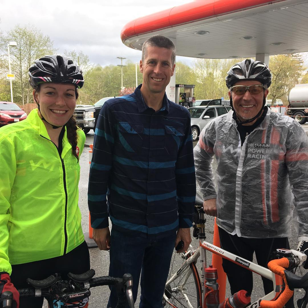 Three people taken outside at a gas station. There is a woman in a yellow jacket (left) a tall man in a blue dress shirt and jeans (middle) and a man in a clear raincoat and HPR black shirt visible through his coat (right). All are smiling and the man on the right has a bike.