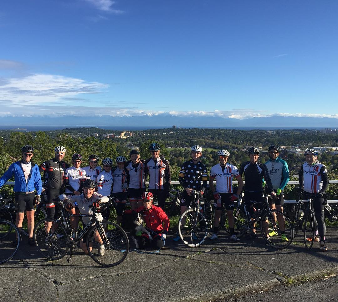 Bikers with their bikes on the top of Mount Tolmie. It shows the large group standing on a road with a blue sky, distant mountains, and the Victoria city scape behind them.