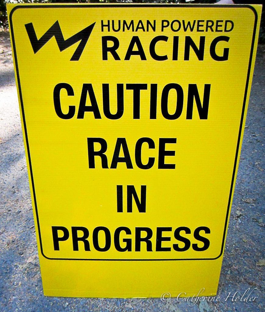 "A bright yellow sign that says ""Human Powered Racing"" at the top next to their logo, which is a zig zag line in the shape of a mountain range silhouette. Beneath that on the sign, and in larger letters, it says ""Caution Race in Progress."" Behind the sign is a gravel covered ground outside."