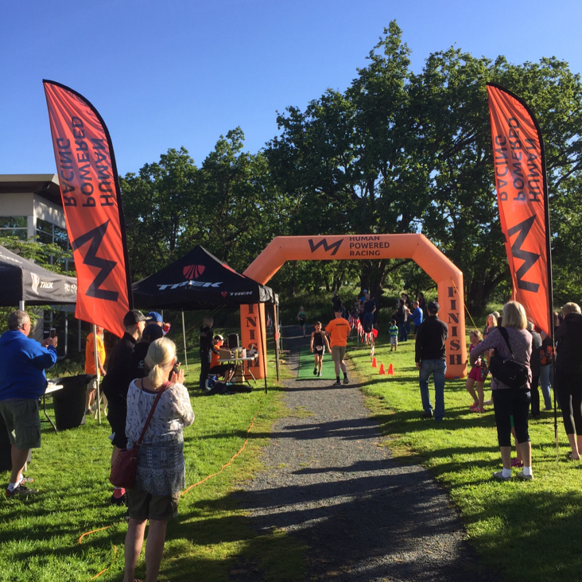 """This is a photo of an orange inflatable finish and start line marker shaped like an archway. It is flanked on either side by tall orange flags that read """"Human Powered Racing"""" and has their logo, which is a line that zig zags like the silhouette of a mountain range. There are people milling about, and a young person crossing the finish line and being given a mental by a man in an orange HPR tshirt."""