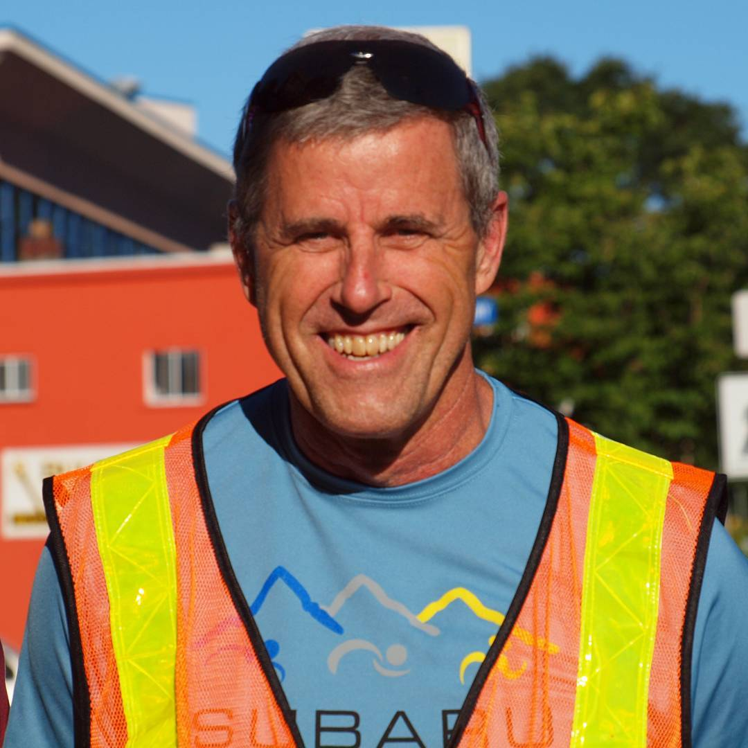 A man in a blue tshirt under an orange and yellow safety vest. We see him from the chest up and he is centred. There is a house to his left and a tree to his right in the backgound and the sky is blue. The background is out of focus. He is tan, and possible a bit sunburnt.