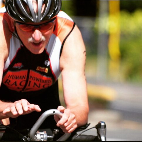 A man leaning over the handle bars on the left is slightly out of focus. We cannot see his bike except for the handle bars. He is in an orange, black, and white human powered racing triathlon suit, and has orange sunglasses and a black helmet. He also has a large white moustache. The background looks like a grey road with green shrubs on the side, but it is very out of focus.