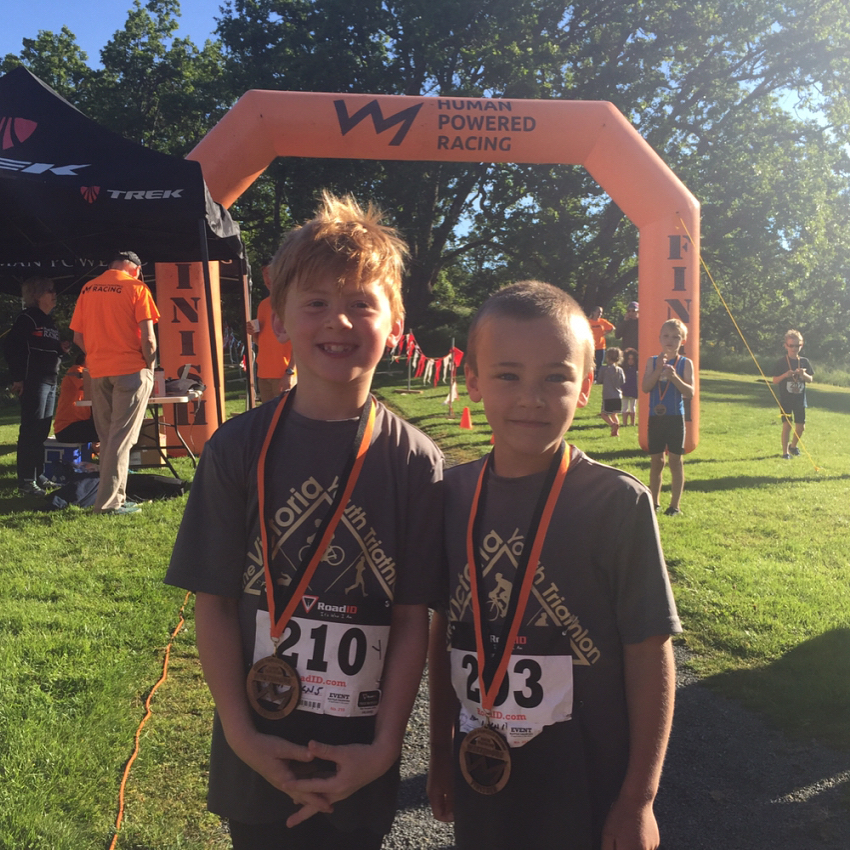 """Two boys standing in front of an orange inflatable finish and start line marker shaped like an archway. It is flanked on either side by tall orange flags that read """"Human Powered Racing"""" and has their logo, which is a line that zig zags like the silhouette of a mountain range. They are wearing wooden metals on black and orange ribbons and smiling. They are standing shoulder to shoulder on green grass with green trees in the background."""