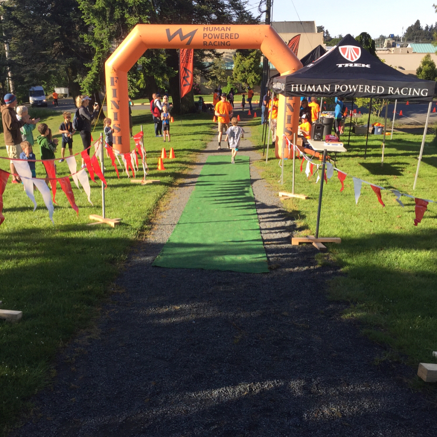 """This is a photo of an orange inflatable finish and start line marker shaped like an archway. It is flanked on either side by tall orange flags that read """"Human Powered Racing"""" and has their logo, which is a line that zig zags like the silhouette of a mountain range. There are people milling about, and a young person crossing the finish line and being given a mental by a man in an orange HPR tshirt. There is a black HPR tent in the foreground. It is a sunny day."""